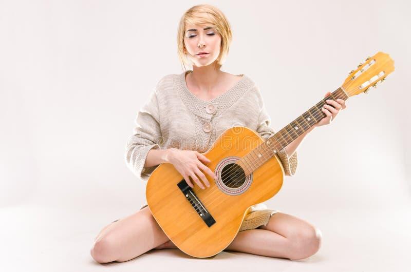Ung härlig le blond dam i den gråa tröjan som spelar den akustiska gitarren royaltyfria bilder