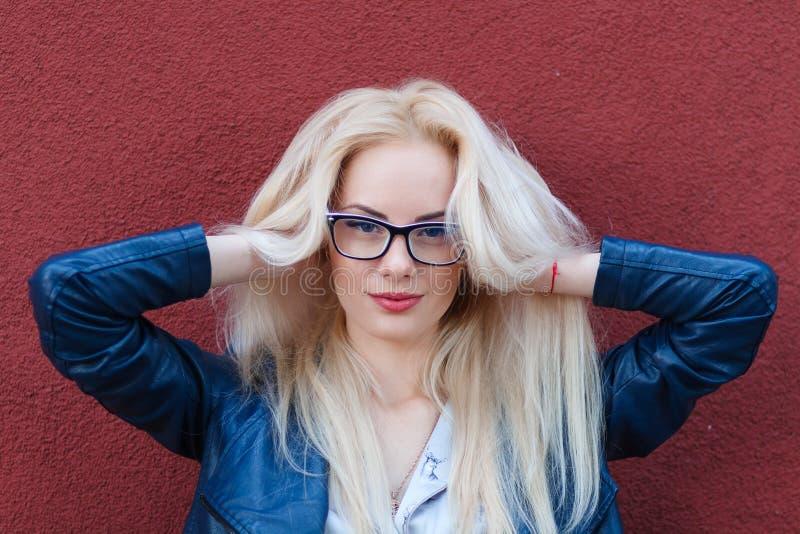 Ung härlig le blond flicka med härligt utseende och långt hår Le flickan i exponeringsglas och en charmig blick arkivbilder