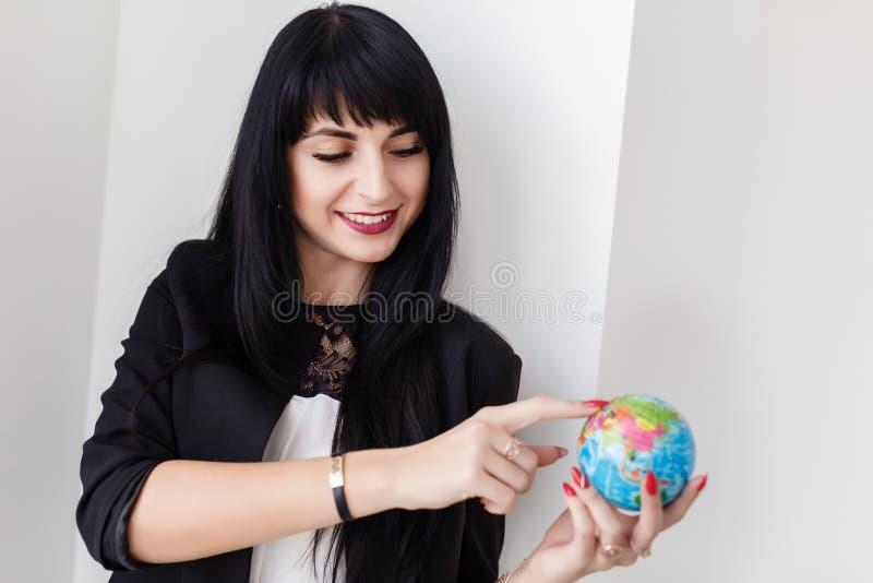 Ung härlig le dräkt för affär för brunettkvinna som iklädd svart rymmer ett jordklot av planetjorden arkivbild