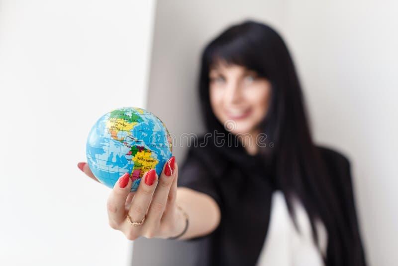 Ung härlig le dräkt för affär för brunettkvinna som iklädd svart rymmer ett jordklot av planetjorden royaltyfri bild