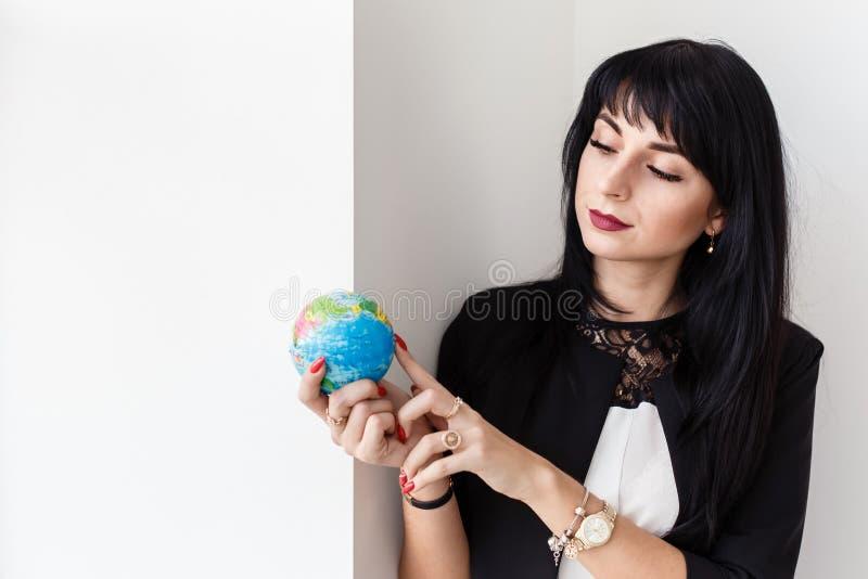 Ung härlig le dräkt för affär för brunettkvinna som iklädd svart rymmer ett jordklot av planetjorden royaltyfri fotografi