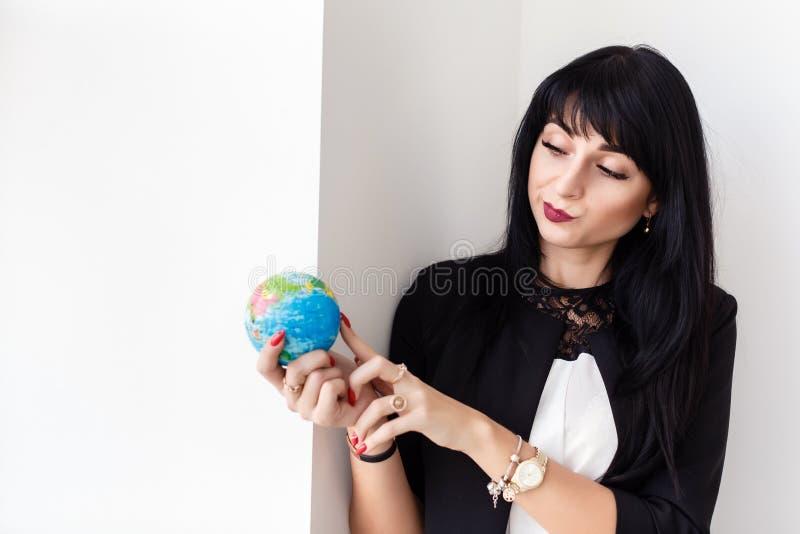 Ung härlig le dräkt för affär för brunettkvinna som iklädd svart rymmer ett jordklot av planetjorden arkivbilder