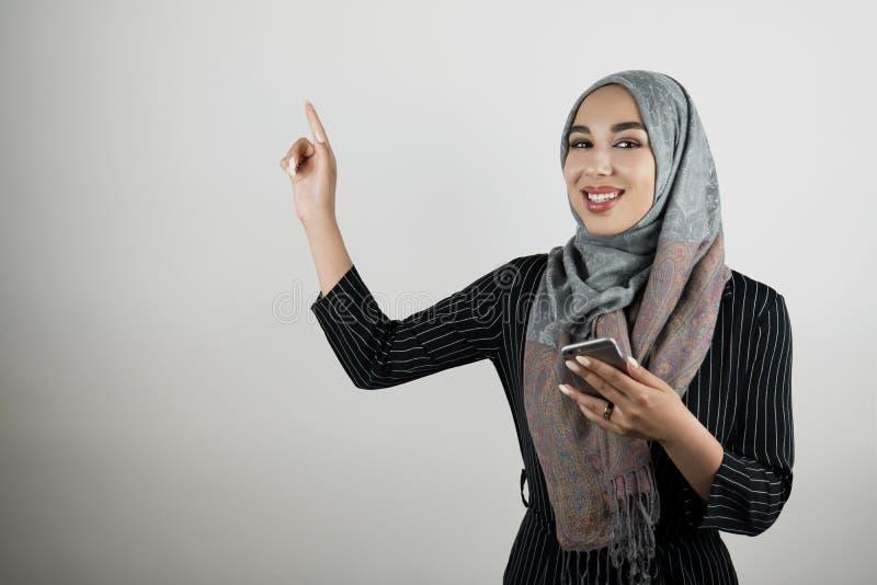 Ung härlig le för turbanhijab för muslimsk kvinna bärande smartphone för innehav för sjalett i en hand och peka med henne royaltyfria foton