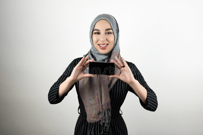 Ung härlig le för turbanhijab för muslimsk kvinna bärande visning för sjalett och rymmasmartphone i hennes händer isolerat royaltyfria bilder