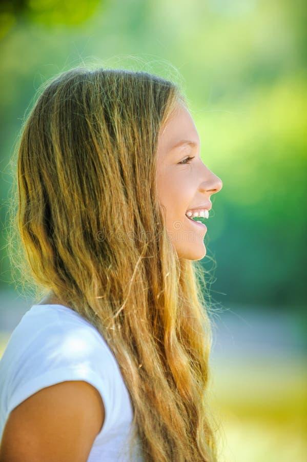 Ung härlig le flicka i profil royaltyfri fotografi