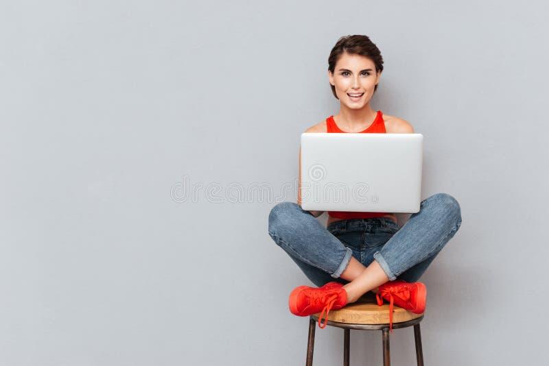 Ung härlig le flicka som använder bärbar datorPCdatoren för studie royaltyfri fotografi