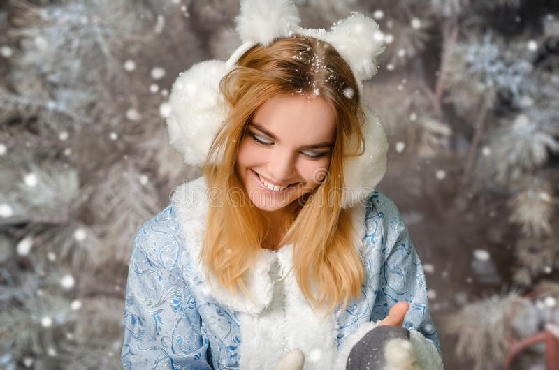 Ung härlig le flickastående i snöig skog för vinter fotografering för bildbyråer