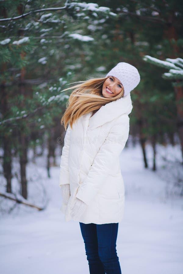 Ung härlig le flickastående i vinterskog royaltyfria bilder