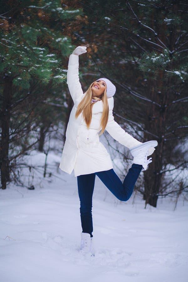 Ung härlig le flickastående i vinterskog royaltyfri foto