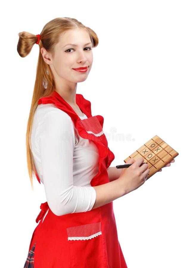 Ung härlig le hemmafru i rött förkläde med rolig ponyta royaltyfria bilder