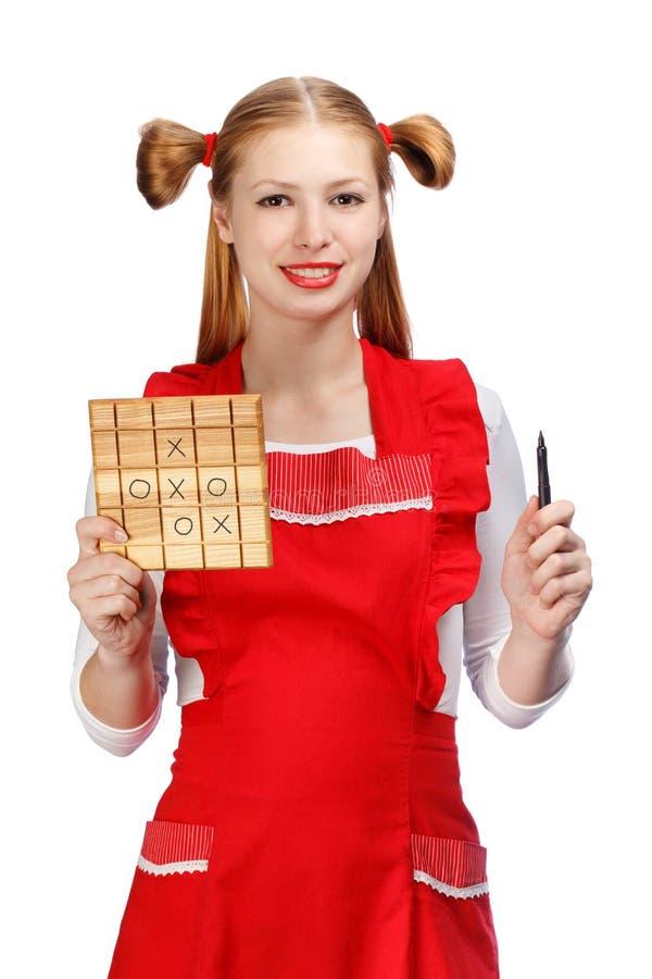 Ung härlig le hemmafru i rött förkläde med rolig ponyta arkivbilder