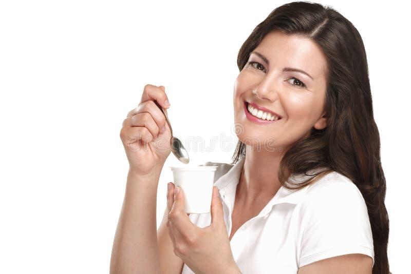 Ung härlig le kvinna som äter ny yoghurt arkivfoton