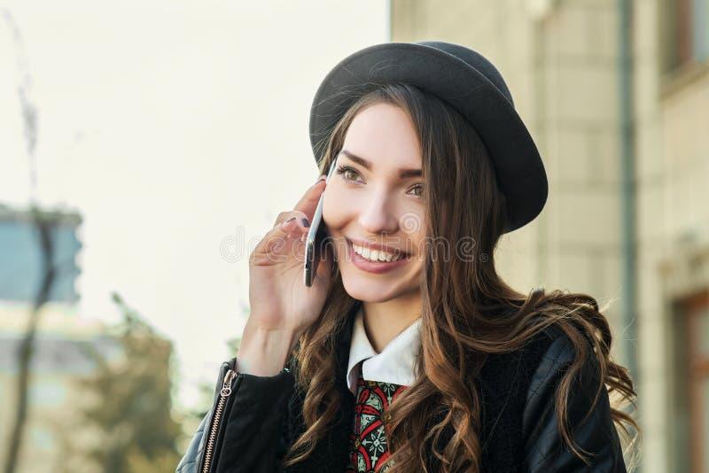 Ung härlig le kvinna som talar på mobiltelefonen arkivbild