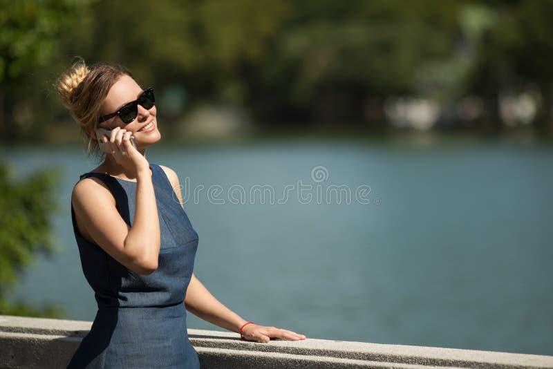 Ung härlig le kvinna som talar på smartphonen royaltyfria foton