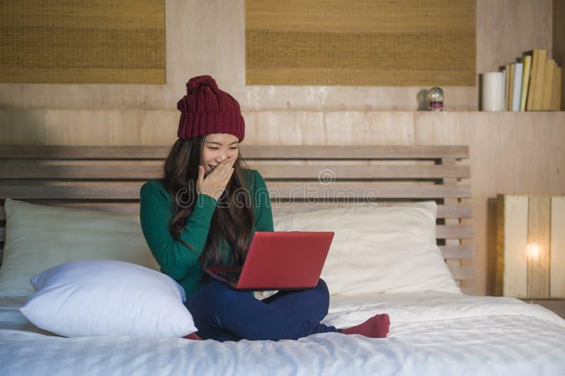 Ung härlig lycklig asiatisk japansk flicka i beamy sammanträde för vinter som kopplas av på säng genom att använda bärbar datorda royaltyfria bilder