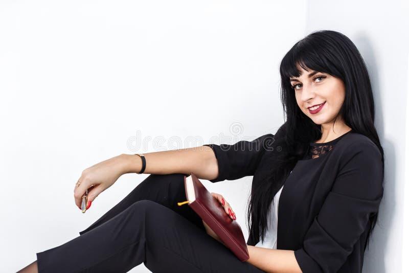 Ung härlig lycklig brunettkvinna som rymmer en anteckningsbok iklädd en svart affärsdräkt som sitter på ett golv i ett kontor som royaltyfri fotografi