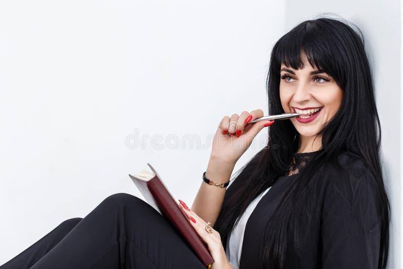 Ung härlig lycklig brunettkvinna som rymmer en anteckningsbok iklädd en svart affärsdräkt som sitter på ett golv i ett kontor som royaltyfri bild