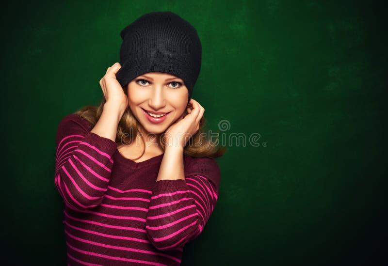 Ung härlig lycklig flickatonåring i en svart på en grön backgr arkivfoton