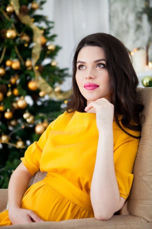 Ung härlig lycklig gravid kvinna i en lång gul klänningsiti royaltyfri fotografi