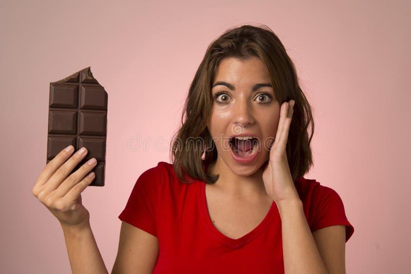 Ung härlig lycklig och upphetsad kvinna som rymmer stora chokladlodisar royaltyfri foto
