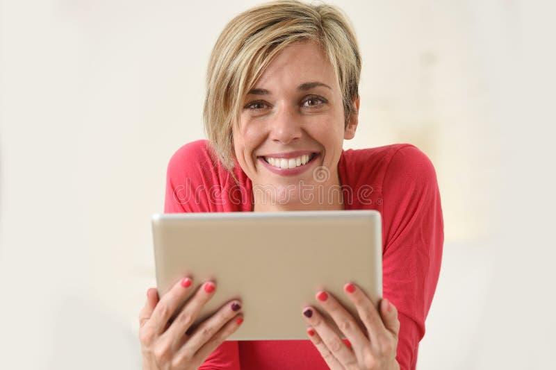 Ung härlig lycklig 30-talkvinna som ler genom att använda soffan för vardagsrum för digitalt minnestavlablock den hemmastadda fotografering för bildbyråer