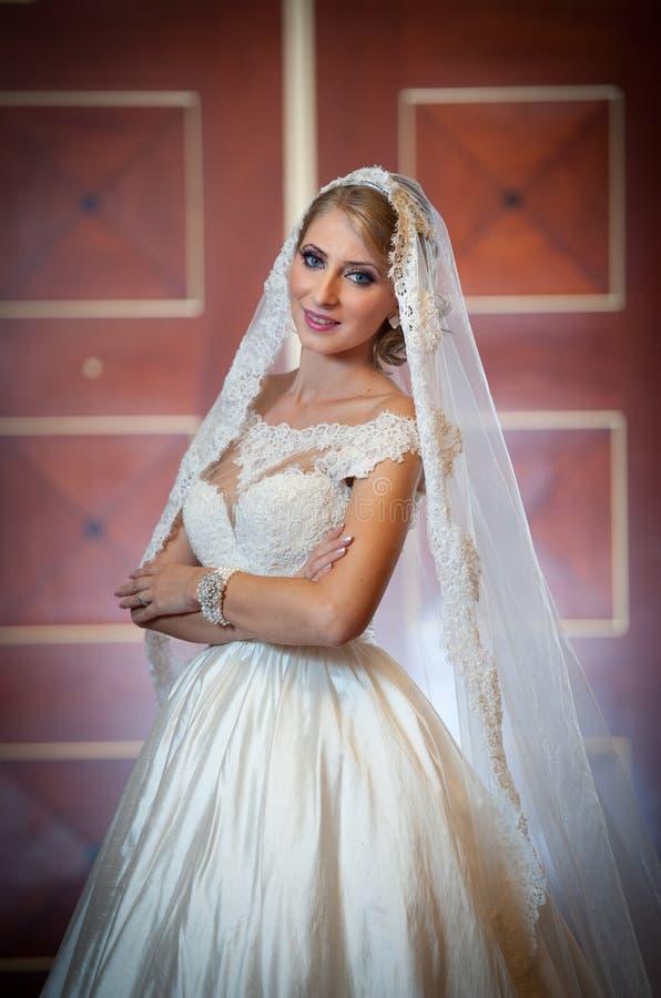 Ung härlig lyxig kvinna i bröllopsklänningen som poserar i lyxig inre Den ursnygga eleganta bruden med länge skyler Full längd arkivfoto