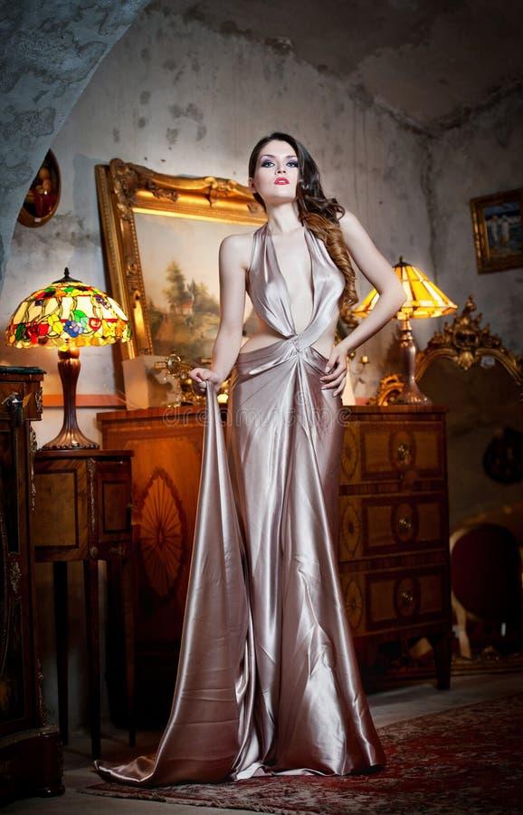 Ung härlig lyxig kvinna i lång elegant klänning. Härlig ung kvinna i en lyxig klassisk inre. Förförisk brunett arkivfoto