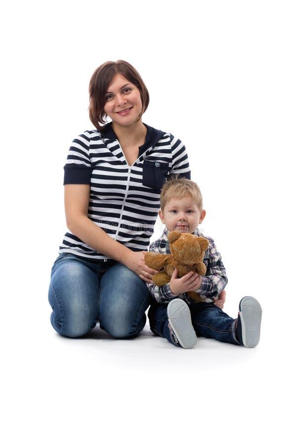 Ung härlig moder i jeans som sitter med hennes son tre år royaltyfria foton