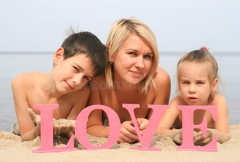 Ung härlig moder med barn som ligger på stranden med ordförälskelse royaltyfria foton