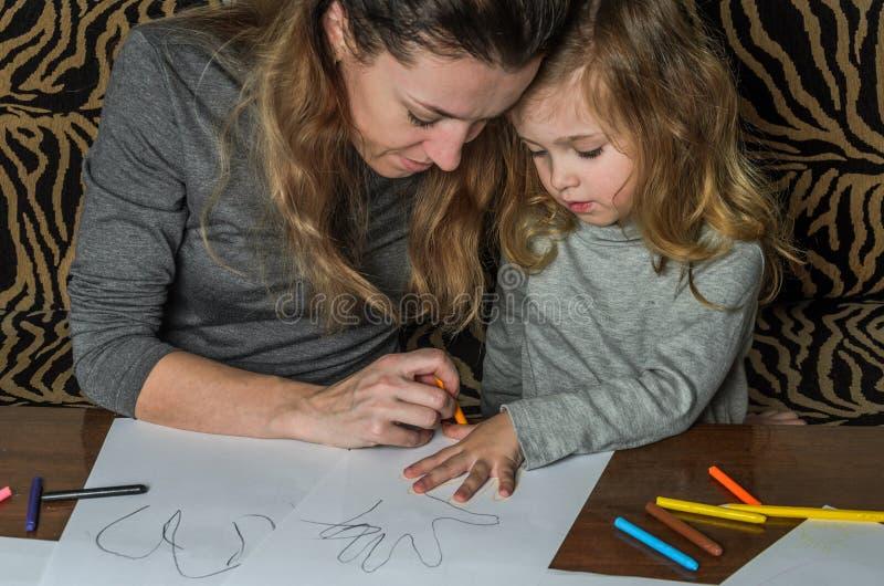 Ung härlig moder med hennes dotterattraktion med färgrika blyertspennor på papper, lycklig familj royaltyfri foto