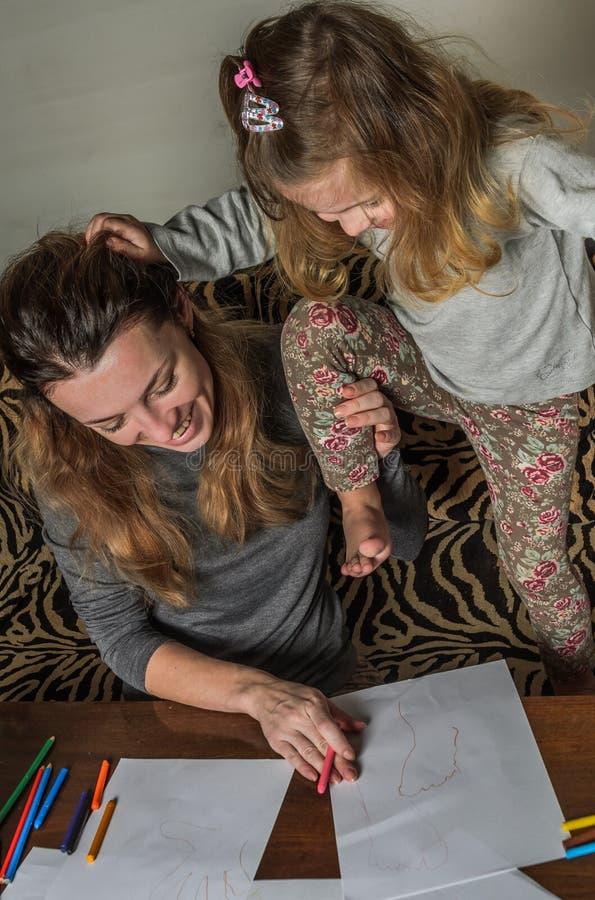 Ung härlig moder med hennes dotterattraktion med färgrika blyertspennor på papper, lycklig familj royaltyfri fotografi