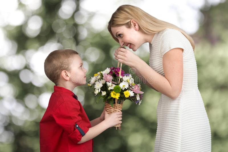 Ung härlig moder med hennes son En kvinna och en behandla som ett barnpojke med en bukett, en korg av blommor Vårbegrepp av famil royaltyfria bilder