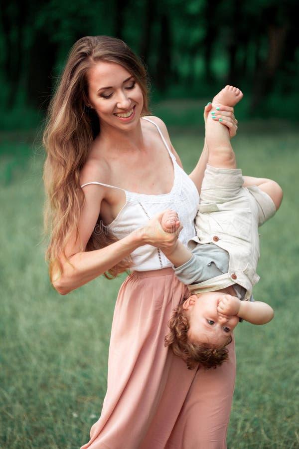 Ung härlig moder som kramar hennes lilla litet barnson mot grönt gräs Den lyckliga kvinnan med hennes behandla som ett barn pojke royaltyfri foto