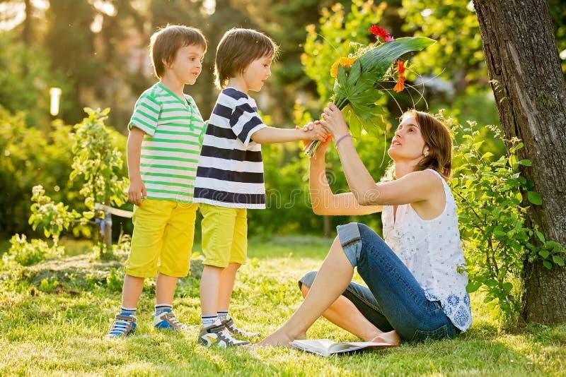 Ung härlig moder som så sitter i en trädgård, pyser, henne royaltyfri bild