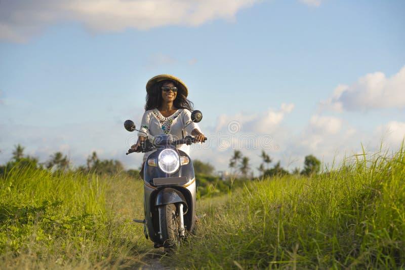 Ung härlig moped för ridning för kvinna för turist- eller nomadhandelsresandesvart afro amerikansk i det tropiska fältet som bär  royaltyfri fotografi