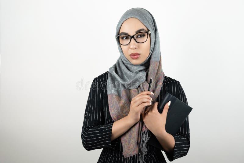 Ung härlig muslimsk kvinna i exponeringsglas som bär turbanhijab, sjalett som rymmer en anteckningsbok och en penna isolerad vit royaltyfri fotografi