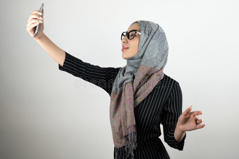 Ung härlig muslimsk kvinna i exponeringsglas som bär turbanhijab, sjalettinnehavsmartphone som skjuter en isolerad selfie royaltyfri foto