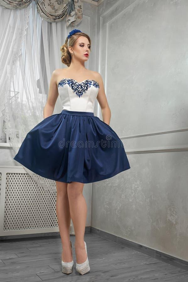 Ung härlig nätt kvinna i den korta blått-och-vit klänningen, mummel arkivfoton