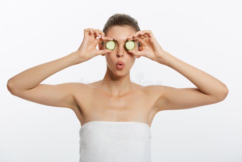 Ung härlig naken flicka som ler nederlagögat bak gurkaskivan som ser kameran över vit bakgrund royaltyfria foton