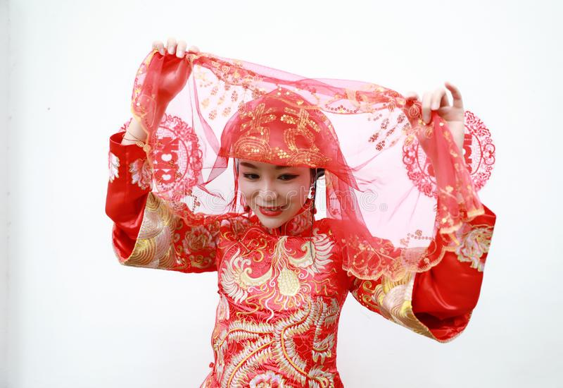 Ung, härlig och elegant kinesisk kvinna som bär en typisk kinesisk bruds siden- röda klänning som smyckas med guld- phoenix och d arkivbilder