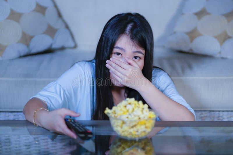 Ung härlig och förskräckt asiatisk japansk tonåringkvinna i soffa för soffa för läskig film för fasa för skräck som hållande ögon fotografering för bildbyråer