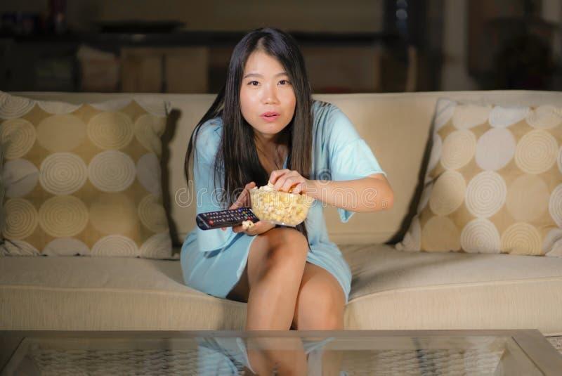 Ung härlig och förskräckt asiatisk japansk tonåringkvinna i soffa för soffa för läskig film för fasa för skräck som hållande ögon royaltyfri foto