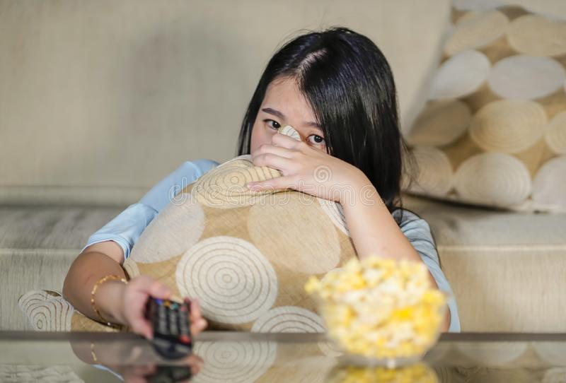 Ung härlig och förskräckt asiatisk japansk tonåringkvinna i soffa för soffa för läskig film för fasa för skräck som hållande ögon royaltyfri bild