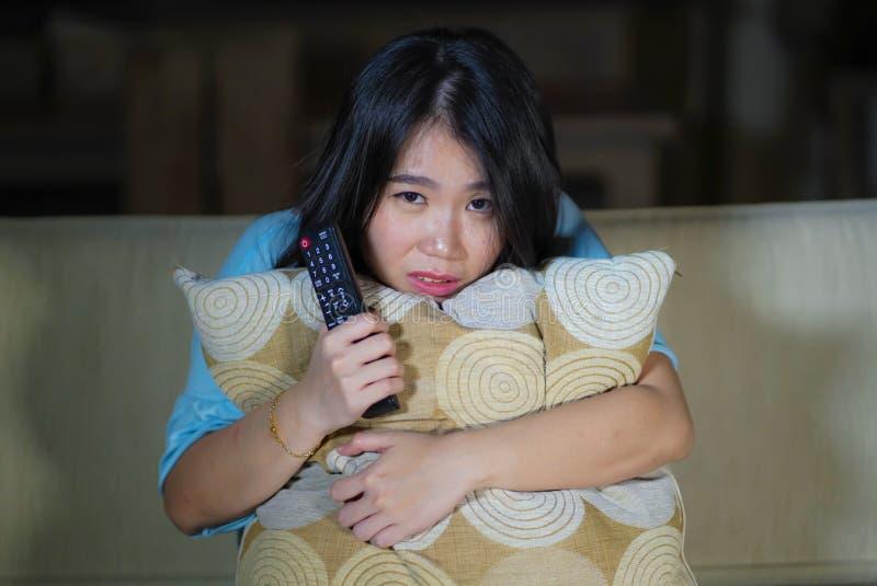 Ung härlig och förskräckt asiatisk japansk tonåringkvinna i soffa för soffa för läskig film för fasa för skräck som hållande ögon royaltyfri fotografi