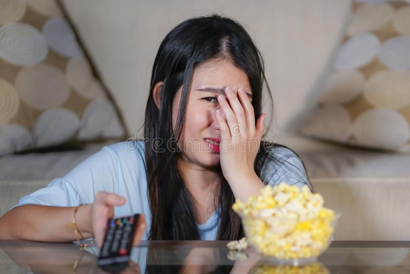 Ung härlig och förskräckt asiatisk kinesisk tonåringkvinna i soffa för soffa för läskig film för fasa för skräck som hållande ögo royaltyfri fotografi