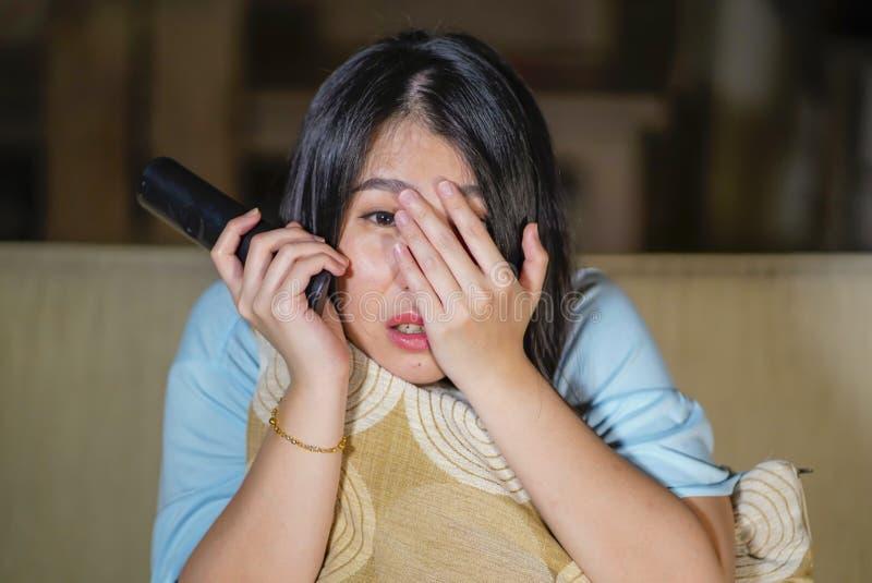 Ung härlig och förskräckt asiatisk kinesisk tonåringkvinna i soffa för soffa för läskig film för fasa för skräck som hållande ögo royaltyfri foto