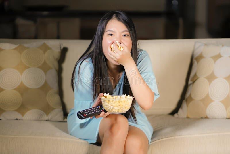 Ung härlig och förskräckt asiatisk kinesisk tonåringkvinna i soffa för soffa för läskig film för fasa för skräck som hållande ögo arkivfoton