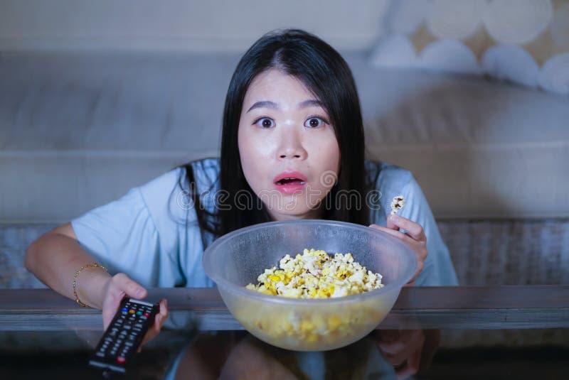 Ung härlig och förskräckt asiatisk kinesisk tonåringkvinna i soffa för soffa för läskig film för fasa för skräck som hållande ögo fotografering för bildbyråer