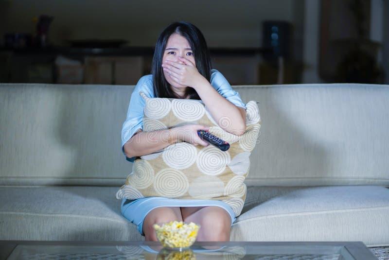 Ung härlig och förskräckt asiatisk koreansk tonåringkvinna i soffa för soffa för läskig film för fasa för skräck som hållande ögo royaltyfria foton