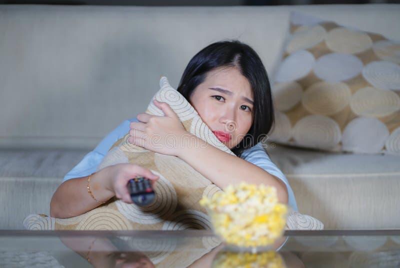 Ung härlig och förskräckt asiatisk koreansk tonåringkvinna i soffa för soffa för läskig film för fasa för skräck som hållande ögo arkivfoton